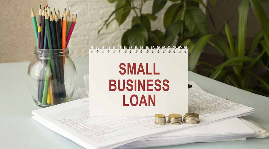small business loan card standing on top of forms